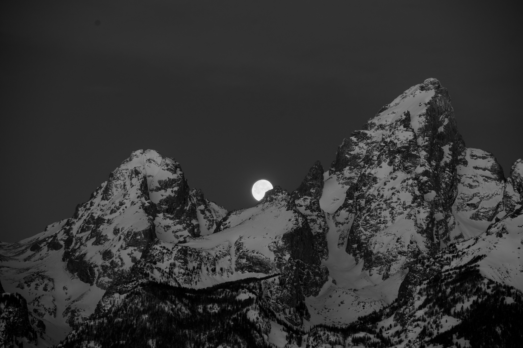 An early photo made of the moon setting between the mountain peaks